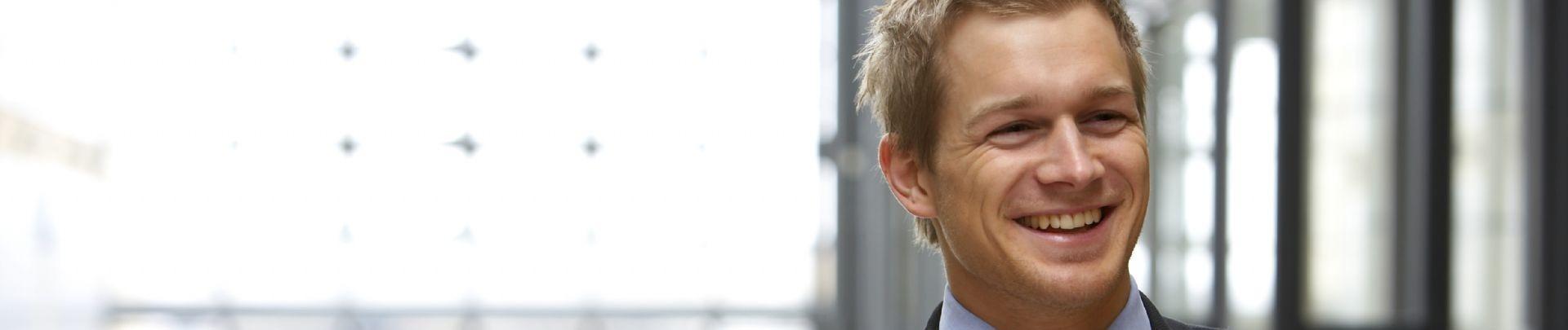 blonde man in pak met blauwe stropdas lacht